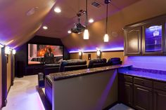 Custom home theater with built-in bar area behind seats and color changing LED lighting details