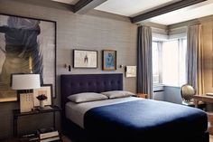 A luxe yet refined bedroom designed by Mark Cunningham boasts beautiful art, grey silk wallpaper, and a simple down home wool blanket. Photo by Christopher Sturman.