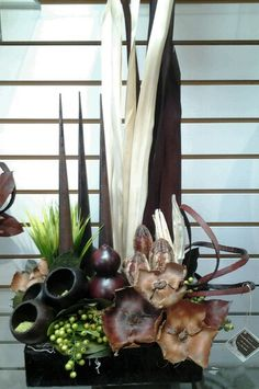 Each arrangement is a one of a kind work of art.  The botanicals are made of dried pods, artificial grasses and on occasion silk orchids.  This is the new style for dry flower arrangement.