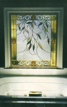 A five foot stained glass windo featuring a cascade of leaves with a classical gold border.
