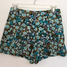 Monteau Los Angeles Shirts HP 5/17 Monteau Los Angeles floral shorts in teal, blue, white, olive / tan and black. Light weight flowy fabric. Quick dry fabric. Cute bow in back. Little pulling a fabric in seams at top of waist. Otherwise great condition. See picture. Waist measurement 13 1/2. hip 19 inches, front inseam 12 inches, Monteau Shorts