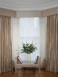 Neutral beige silk curtains in a bay window with matching upholstered pelmet.