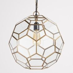 Intricately crafted of clear glass panes set in an antique brass frame, our exclusive pendant's honeycomb contours are reminiscent of a geometric terrarium. Pair it with one of our vintage-style filament bulbs for an on-trend accent.