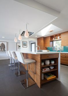 Geometric Pendant Lights, Woodgrain Cabinetry and White Leather Bar Chairs in Midcentury Modern Kitchen