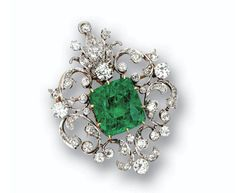 EMERALD AND DIAMOND PENDANT-BROOCH, BLACK STARR & FROST, CIRCA 1910.  The scrollwork cartouche set with 71 old European-cut, old-mine and single-cut diamonds weighing approximately 4.25 carats, set in the center with a cushion-shaped emerald weighing approximately 20.00 carats, mounted in platinum and gold, engraved with initials H.H.B. to E.R.U.B., signed B.S& F., brooch fitting detachable.