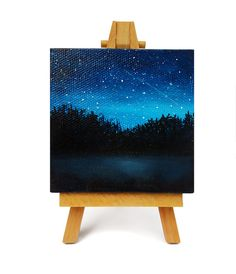 An original little lake silhouette painting. This is acrylic on canvas, signed on the back side, and measures 3 x 3 inches. A miniature easel is