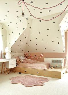 Podest ze schowkami zastąpił w tym dziecięcym pokoju standardowe łóżko. Ścianę pomalowaną na różowo zestawiono ciekawie z szarymi grochami, które namalowano na skosach i suficie. Nastrój we wnętrzu tworzy świecąca girlanda i lampa w kształcie lalki kokeshi, ustawiona na biurku.