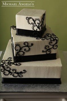 Black Swirl & Shimmer #77Ribbons This three-tier cake creation is designed so that each layer is on an angle. The cascading swirl placed on the corners also give it a very elegant appearance. Shimmer was sprinkled on each layer for a slight glisten.