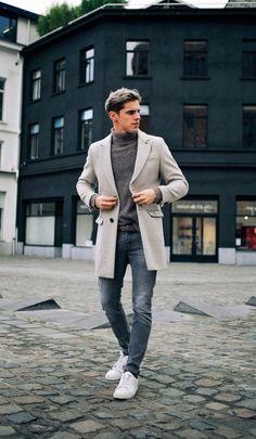 Cooles Outfit mit grauem Rollkragenpulli, Jeans, hellgrauem Wollmantel und weißen Sneakers.