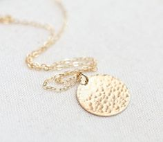 She'll love this gold pendant necklace. It's very dainty and something that can be worn daily.     Tiny hammered gold filled disc on 14k gold filled 20 inch chain.    Perfect gift for Sweet 16, graduation, birthdays, or Mother's Day.     Comes ready for gifting.   I offer free gift wrapping. Just leave a note at checkout.    GOLD-FILLED JEWELRY:  - Under normal wearing conditions and with proper care, your gold filled jewelry should last at least 10 years.  - 14kt Gold-Filled jewelry is made…