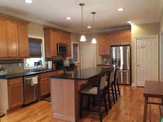 fridge wall Traditional Kitchen with Stone Tile, L-shaped, Hardwood floors, Slate counters, Kitchen island, High ceiling, Crown molding