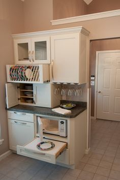 Adding a pull-out shelf below the microwave adds convenience and safety for handing hot foods. (WiFIVE architects)