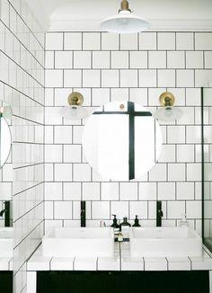 Τα φωτιστικά από ορείχαλκο προσθέτουν στιλ σε αυτό το μπάνιο που έχει 'ντυθεί' με τετράγωνα πλακάκια.