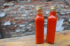 Zelfgemaakte Sriracha met: 500 g rode pepers, 450 ml witte azijn, 2 el keukenzout, 2 el palmsuiker, 8 teentjes knoflook en optioneel citroengras, gember of extra knoflook