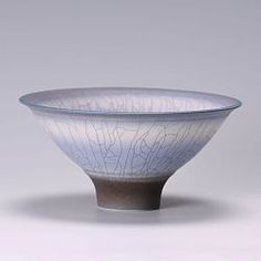 This is a porcelain thrown pot in blue with a wavy top by David White. David uses up to six glazes on one pot to get this extraordinary crackled glaze effect and he often glaze fires his pots until he is satisfied with the results. SOLD