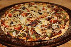 Mexican Beef Pizza (Crisp Crust, Taco Beef with Salsa and Garlic, Mozzarella Cheese, Shredded Yellow Onion, Chopped Poblano Pepper, Sliced Mushrooms, Cherry Tomatoes, Black Olives, Red Pepper Flakes)