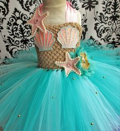 Gorgeous teal, pink and gold accent mermaid costume/party dress for any little girl looking to make a big splash! The dress is knee in length and lined all the way through for comfort! This dress is also dusted with gold glitter to make it that much more special. Processing times for