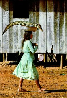 Cool how ordinary it is for this girl to be walking with a gator on her head.