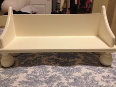 Simple American girl bed. It is a wall shelf purchased at a garage sale for $3.00 and curtain rod finials also garage sale finds for $2.00 a set. Just flip shelf upside down and drill 4 holes in each corner to screw in the finials. (This would make a great couch if you upholstered it!)