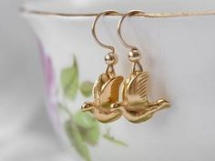 Birds in flight.  These small birds are handmade and plated in 22ct gold.  Hook fastening allow the birds to drop down below the lob slightly are though they are flying through the air when worn.  Light in weight these birds are a charm to wear.