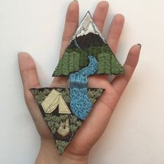 A+hand+embroidered+patch+to+show+your+love+for+camping+in+the+mountains+and+also+groovy+triangles. The+bright+shining+silver+sky+lights+up+white+snow-capped+mountains,+which+overshadow+deep+woods.+A+bright+mountain+stream+winds+its+way+down+from+the+mountaintops+and+down,+across+a+steep+waterf...