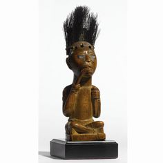 A Yombe Seated Figure, Democratic Republic of the Congo and Republic of the Congo the human figure seated with crossed legs and biting a root held with the right hand, with a piece of skin and hair from the waterbuck antelope (kobus ellipsiprymnus) inserted in the head; 'FX9440' in white pigment on bottom of figure; fine aged honey brown patina.   height 6 1/2 in. 16.5 cm