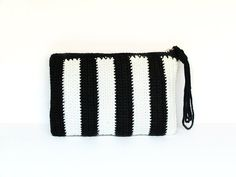 Black and white striped crochet clutch (wristlet) with strap. Bolso de mano de ganchillo hecho a mano por Silayaya. Clutch en rayas blancas y negras.