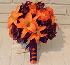 """This """" MADE TO ORDER"""" Tiger Lily Bridal Bouquet has been created with One purple hydrangea, Orange/Tangerine tiger lilies, purple zinnias and small orange peonies. The beautiful handle has been wrapped with tangerine/orange satin ribbon accented with a purple ballerina satin ribbon, finished with a hand tied ribbon bow. Measures approximately 12"""" Wide x 11 """" Tall Accompanied by a complimentary grooms boutonniere. If you need additional items such as groomsmen boutonnieres, toss bouque"""