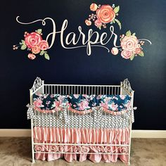 Blush and Navy nursery the painted flower accent wall the contrast of the soft pink crib skirt is divine
