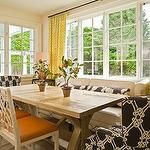 dining rooms - captain chairs yellow citrine Kelly Wearstler Imperial Trellis fabric drapes ivory leather settee sofa nailhead trim rustic wood trestle dining table ivory fretwork dining chairs orange cushions ornage gourd lamp