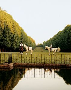 The front lawn of Valentino's Château de Wideville, near Paris, with grooms exercising his three horses, Dean, Equador, and Blue Boy.