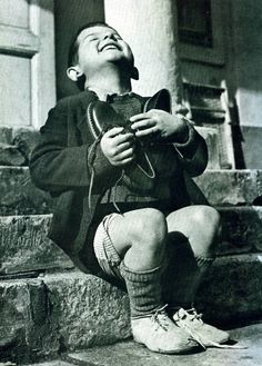 Werfel, a 6 year old orphan from Austria after being given his first pair of new shoes by the American Red Cross in 1946