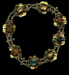 Necklace, 14th Century Museu Nacional de Machado de Castro. Coimbra, Portugal This rare gold necklace, enriched by the contrasting colours of the precious stones, belonged to the bequest of the Queen, Saint Isabel. It consists of 8 multi-lobed plates, linked by two parallel chains and accented by 9 baroque pearls in groups of 3. The central gems (3 sapphires, 1 glass, 1 glass doublet and 2 topazes) are surrounded by a collar, encircled on the base with a typical medieval setting of small…