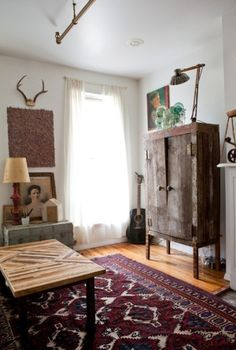 White walls, wood furniture, patterned rug, industrial lighting, eclectic wall decor.