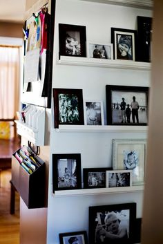 Photo display using floor to ceiling shelves and frames. What a great way to change out some of the photos a few times a year!