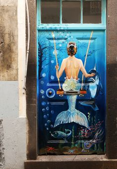 Funchal, Madeira, Portugal- An ordinary wooden door, decorated with a painting depicting a beautiful mermaid