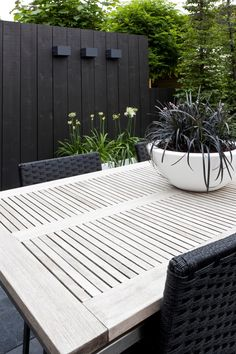 Kleine moderne tuin hoekwoning Black wall and white table interspersed with greenery, beautiful. Pinned to Garden Design by Darin Bradbury.