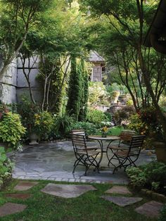 A stone patio shaded by trees is an ideal outdoor setting for a small dining area.
