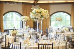 We love the use of the tall, clear vases so that the color of the flowers is the focal point of the centerpieces on each table. Photo Credit - Tiffany Wayne Photography