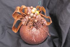 Copper colored ornament decorated with pine cones and miniature ornaments