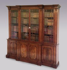 A fine quality George III period well-figured mahogany Breakfront Bookcase in the manner of Gillows of Lancaster, having bold moulded cornice above glazed doors flanked by columns and flame figured panelled doors below, ending on plinth base. Circa 1800 Ref: Brkfront Bkcase