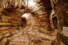 Túnel feito de madeira na nova instalação do artista paulista Henrique Oliveira, no MAC