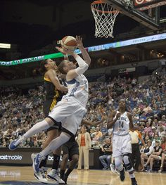 Minnesota Lynx guard Lindsay Whalen goes in for a lay-up over Tulsa Shock forward Nicole Powell. (Photo by Matthew Fleegel)