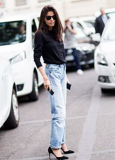 A black sweater is worn with high-waisted light wash jeans and black pumps