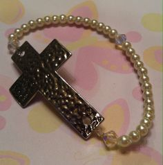 Faith Cross Bracelet Sideways silver tone hammered cross with 4mm white pearl finish glass beads & Swarovski crystals made on stretch cord. $10.00