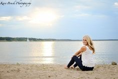 2014 High School Senior girl for posing picture ideas. Senior girl sitting on a beach by the lake at sunset with a sailboat in the background. High school senior session pose inspiration for senior pictures.