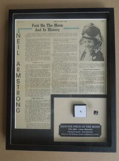 Large display with a vintage newspaper article about the first lunar landing,. The specimen in the lower-right corner is a moon rock (lunar meteorite).