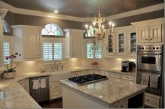 Someday.... kitchen with white cabinets, white and light gray granite counters, chandelier, gray walls, farmhouse sink, stainless appliances