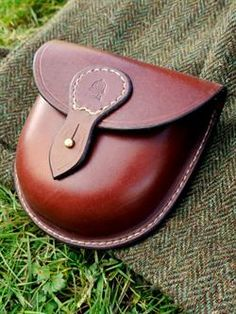 """Medium Possibles Pouch £52.00 This Hand stitched leather pouch comes with a brass Sam Browne stud closure on and belt loop for attachment that sits on the belt line.  Ideal as a store for your first aid kit, tinder, fire steel or camera, it is available in five colours options.   5"""" x 5"""" x 1.25"""""""