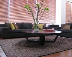 want circular coffee tables  Exotic Spacious Living Room with Artistic Decoration and Glass Wall: Cozy Modern Living Room With Circular Coffee Table And Floral Carpet